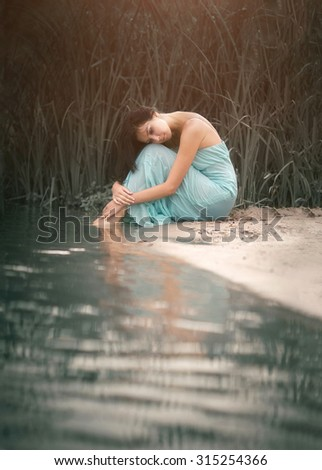 Charming and romantic girl sleeping and dreams near the water stream. Outdoor. - stock photo