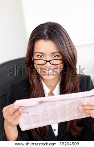Charming asian businesswoman holiding a newspaper smiling at the camera in her office - stock photo