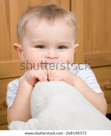 Charming baby boy portrait with white soft plush toy - stock photo