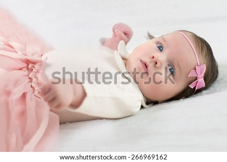 Charming baby girl with diadem lying on his back  - stock photo