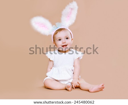 Charming baby sitting in costume easter bunny - stock photo