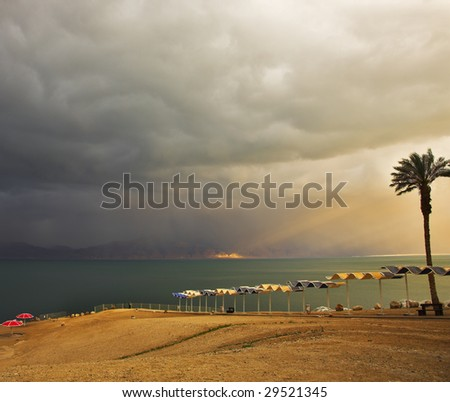 Charming beach canopies on deserted coast of the Dead Sea in a thunder-storm