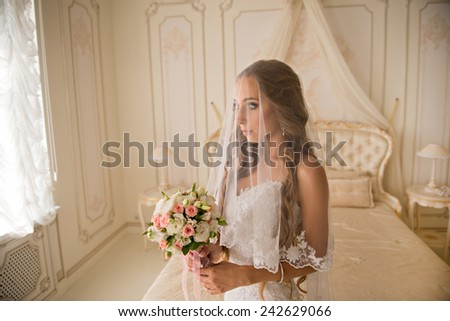 charming beautiful bride holding wedding bouquet in her hands. bride in white dress in a luxury interior, near the beautiful white bed. Bride in beautiful white veil