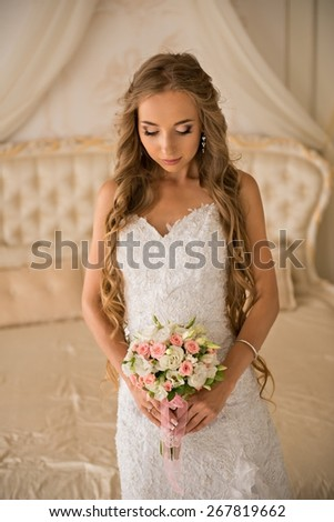 charming beautiful bride holding wedding bouquet in her hands. bride in white dress in a luxury interior, near the beautiful white bed