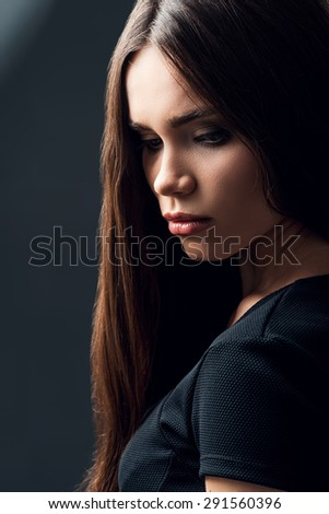 Charming beauty. Attractive young woman with long hair looking down while standing against black background