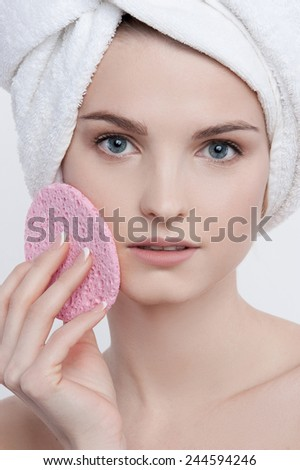 Charming beauty portrait of blue-eyed young woman with natural make-up, french manicure  and clean skin with white towel on her head and pink rough sponge in her left hand closing her left cheek. - stock photo