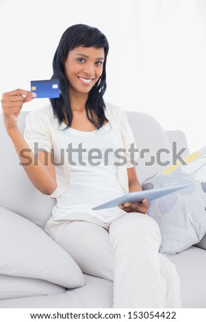 Charming black haired woman buying online on her tablet pc in a living room - stock photo