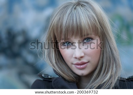 Charming blond haired women headshot against grungy wall - stock photo
