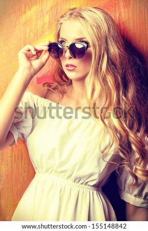 Charming blonde girl in romantic white dress and sunglasses over vivid background. - stock photo