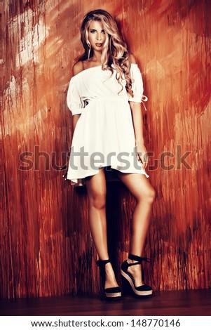 Charming blonde girl in romantic white dress over vivid background. - stock photo