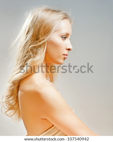 Charming blonde girl's face in the profile