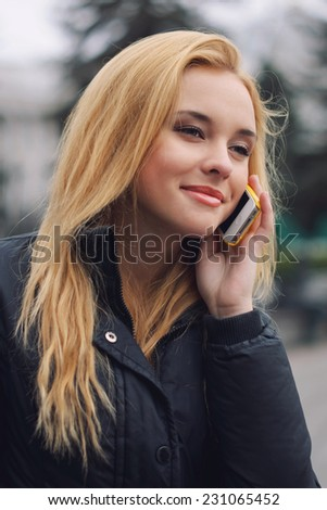 Charming blonde girl smiles and talks on mobile telephone - stock photo
