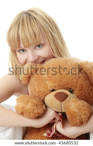 Charming blonde in bed embraces teddy bear isolated - stock photo