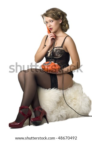 Charming blonde in the style pin up with old phone