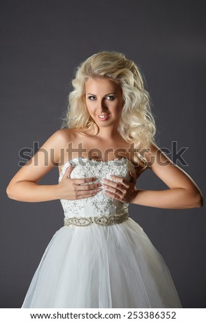 Charming bride holding hands on her breasts - stock photo