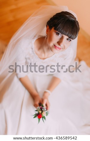 Charming bride in gorgeous white dress waiting for her wedding posing with cute floral boutonniere - stock photo