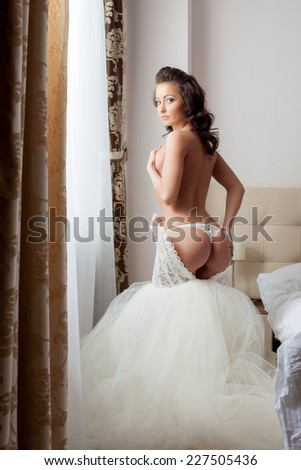 Charming bride undressing at camera in hotel room - stock photo
