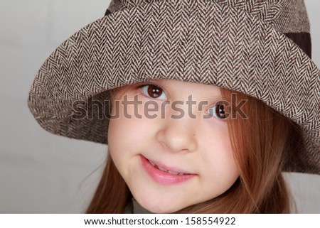 Charming brown hair little girl in a beautiful autumn stylish hat