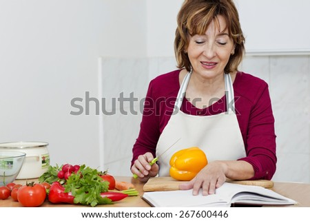 Charming brown haired mature woman reading a cookbook and preparing food of freshness vegetables. - stock photo