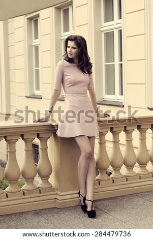 charming brunette girl posing in fashion outdoor shoot with trendy pink dress and heels. Natural hair-style, stylish make-up