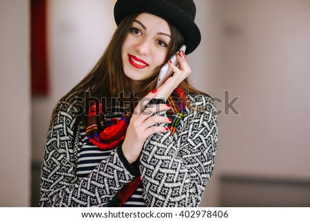 Charming brunette girl talking on a smart phone. Female artist in the exhibition. Beautiful woman hipster in a hat and red scarf talking with a smile on the phone with relatives. - stock photo