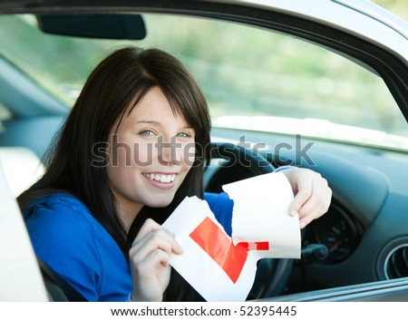 Charming brunette teen girl sitting in her car tearing a L-sign after having her driver's licence - stock photo