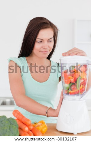 Charming brunette using a blender in her kitchen - stock photo