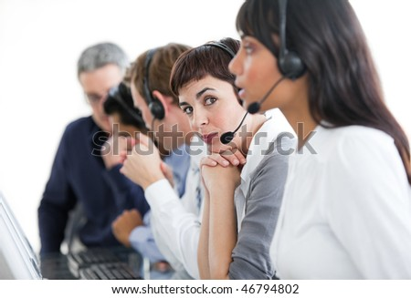 Charming businesswoman with headset on in a call center with her team - stock photo
