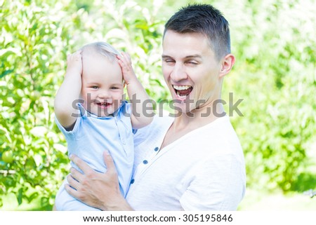 charming caucasian baby boy with father in garden high key - stock photo