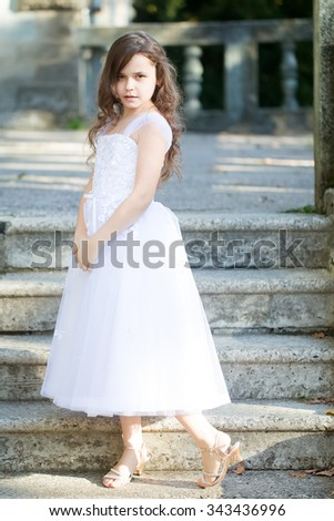 Charming caucasian little bridesmaid with loose dark curly hair in beautiful white fluffy dress in sandals standing on stone stairs background, vertical photo - stock photo