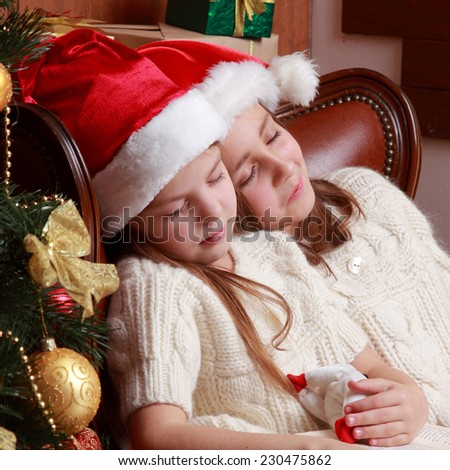Charming caucasian sisters with red and white Santa's hats sleeping snuggled together Holiday theme - stock photo