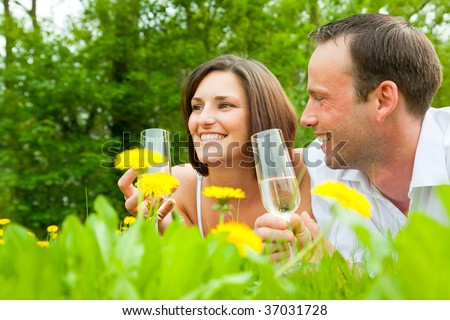 Charming cheerful smiling couple in green park drinking champagne on valentine day
