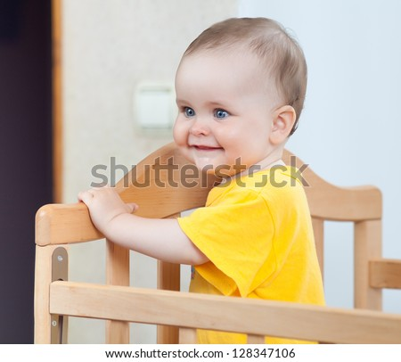 Charming child in the crib. Charming baby in yellow looking away