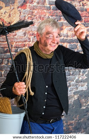 Charming chimney sweep greeting with his cap - stock photo