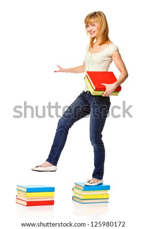 Charming college girl walking from top to top of book piles. Isolated