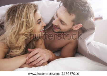 Charming couple covered with a duvet - stock photo