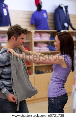 Charming couple looking for a sweat-shirt in a clothes store - stock photo