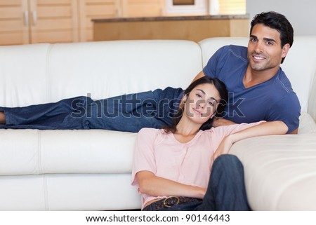 Charming couple posing in their living room - stock photo