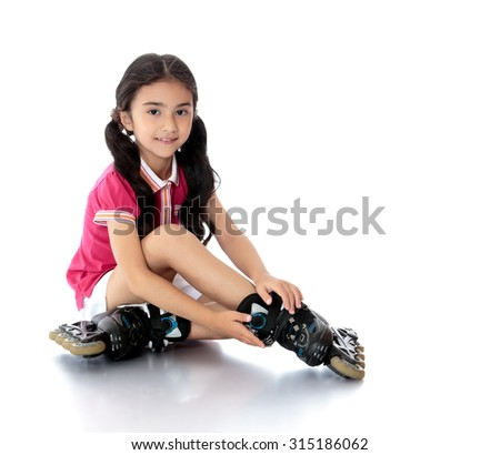 Charming dark-haired girl of preschool age in short white shorts and a pink t-shirt sitting on the floor and tries to foot roller skates. -Isolated on white background - stock photo