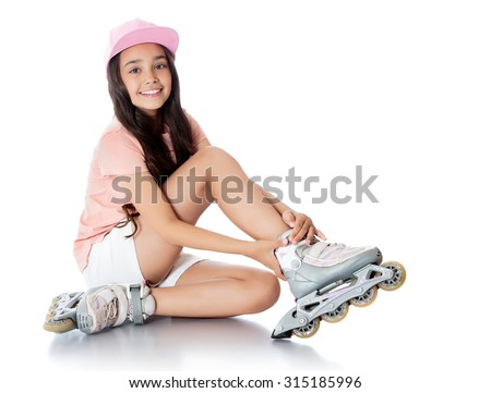 Charming dark-haired girl of school age in short white shorts and a pink t-shirt sitting on the floor and tries to foot roller skates. -Isolated on white background - stock photo