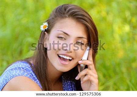 Charming dark-haired happy young woman sitting on grass and talking on cell phone, against background of summer green park. - stock photo