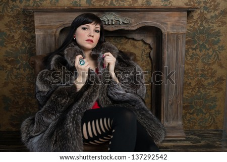 Charming dark-haired lady wearing fur coat and sitting in a vintage room - stock photo