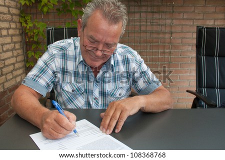 Charming Dutch male senior citizen with a smile on his face signing a legal document in his backyard in the Netherlands