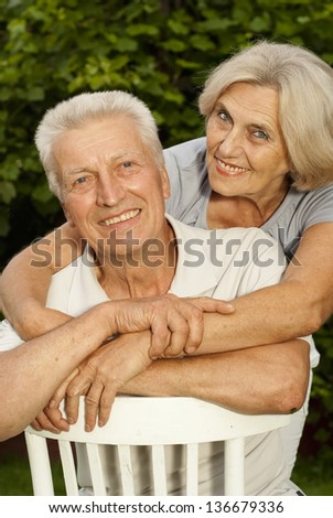 Charming elderly couple in the park on a background of green trees and bushes