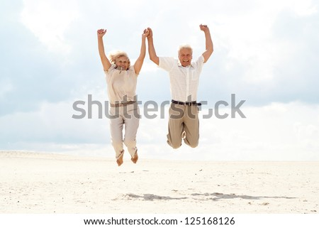 Charming elderly couple went to the beach to enjoy the sea breeze - stock photo