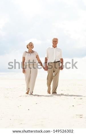 Charming elderly couple went to the beach to enjoy the sea breeze - stock photo