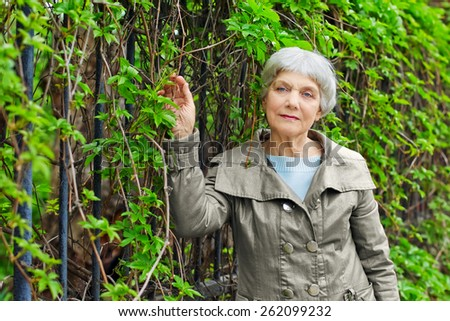 charming elderly woman senior in a park with foliage.
