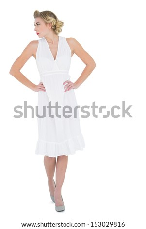 Charming fashion blonde model posing with hands on the hips on white background - stock photo