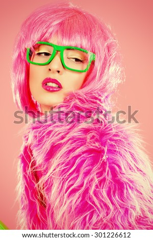 Charming fashion model alluring in sexy colourful clothes. Bright fashion. Pin-up, pink style. Optics, eyewear. Studio shot. - stock photo