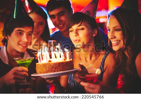 Charming female blowing on candles on birthday cake after making her wish at party - stock photo